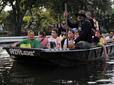 An army boat ferries flood victims to safety on a flooded road in Pinklao district, Bangkok, Thailand on November 4, 2011.