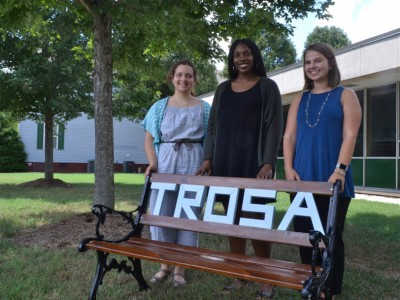 "DGHI interns stand by a bench that reads ""TROSA"" in Durham."