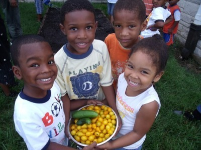 Children holding a bowl of fresh vegetables