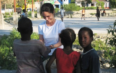 Duke student with children on the street in Leogane