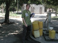 Marc Jeuland stands in front of a hand water pump in Mozambique.