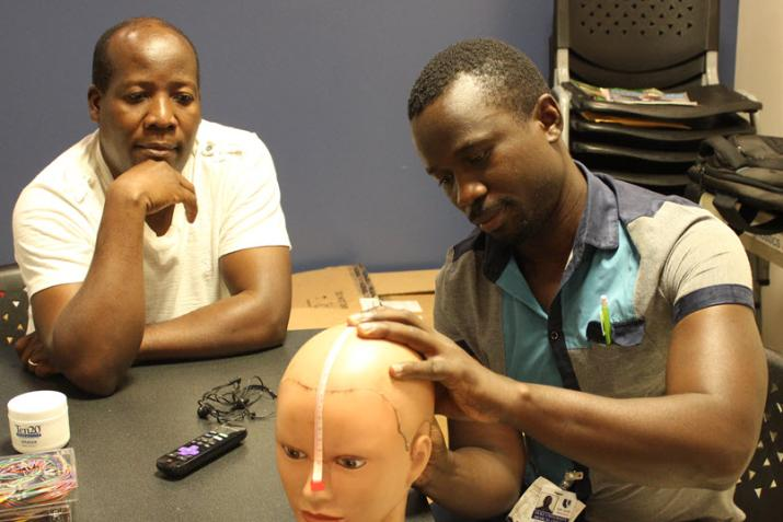 Christopher Komakech demonstrates how to place electrodes for an EEG exam