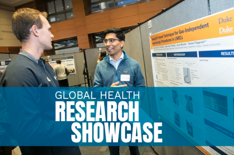 Male student standing in front of research poster presenting to a man